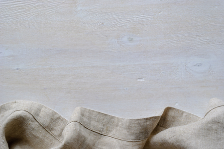 Bottom linen fabric border in a natural neutral woven material over painted white wood with copy space