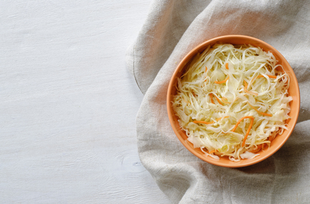 Top view of orange bowl of sauerkraut with chopped cabbage and carrot on grey towel sitting on white table surface Stock Photo