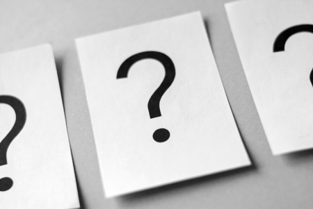 Row of black question marks printed on white sheets of paper viewed in close-up on grey background