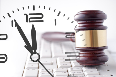 Judges or auctioneers wooden and brass gavel on a white computer keyboard and clock composite in a conceptual image