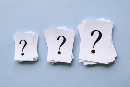 Three piles of question marks printed on white paper in different sizes arranged in a row on a blue background in a conceptual image Banco de Imagens - 122257131