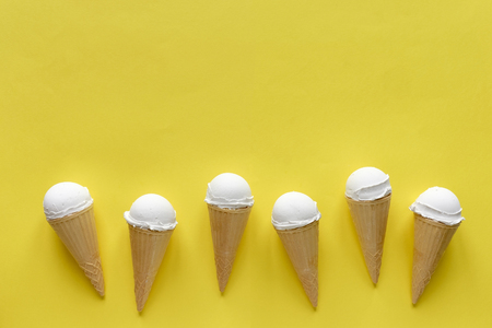 Row of six vanilla ice cream cones on yellow forming a lower border with copy space above for summer food themes