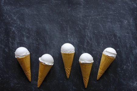 Border of five ice cream cones with delicious creamy vanilla ice-cream arranged on a textured dark grey background with copy space