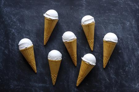 Neat arrangement of seven ice cream cones with frozen Italian vanilla gilt or ice-cream on a textured grey background
