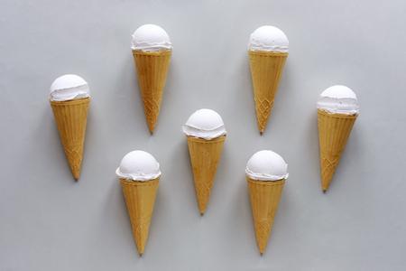 Seven cornets with vanilla ice cream on grey arranged symmetrically around a center cone in a flat lay still life