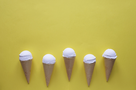 Row of five vanilla ice cream cones on yellow forming a lower border with copy space above for summer food themes