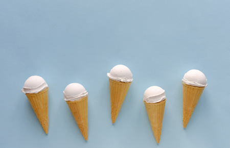 Row of five vanilla ice cream cones on blue forming a lower border with copy space above for summer food themes