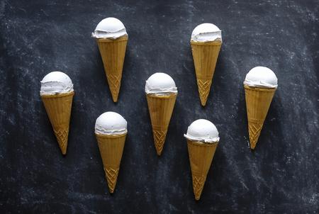 Neat symmetrical arrangement of seven ice cream cones with frozen Italian vanilla gelato or ice-cream on a textured grey background