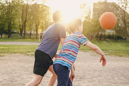 Two young boys enjoying a game of basketball challenging each other for the ball backlit by the bright flare of a warm spring sun behind their heads Imagens