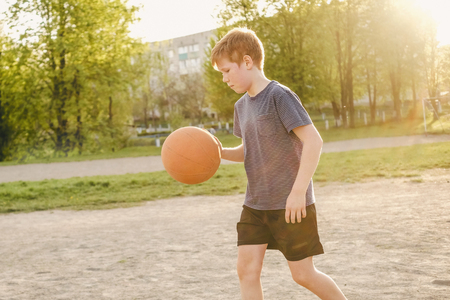 Young basketball player running with the ball bouncing it as he practices his game on a rural sports field by the glow of the evening sun on a warm spring day Reklamní fotografie