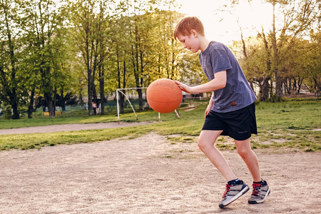 Happy young boy practicing his basketball bouncing the ball as he runs across a sports field in early spring backlit by a warm glow from the sun
