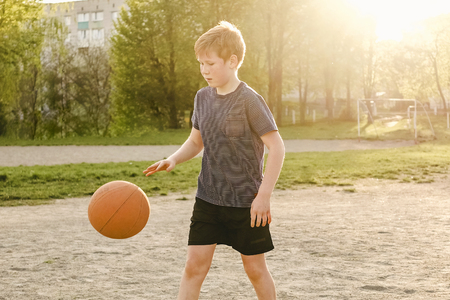 Young basketball player running with the ball bouncing it as he practices his game on a rural sports field by the glow of the evening sun on a warm spring day