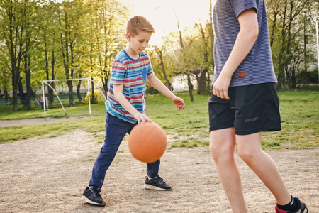Two young boys practicing their basketball outdoors on a rural sports field in a view past the one boy of the second bouncing the ball backlit by the glow of the sun
