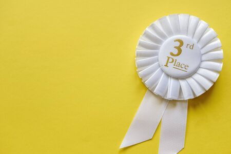 3rd place white ribbon rosette with gold text for the runner up in a competition or race on a yellow background with copy space Stock Photo