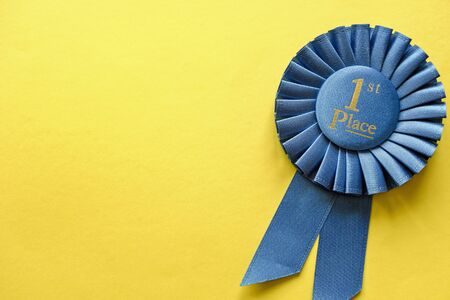 Blue ribbon rosette for the First Placed Winner of a race, championship or competition over a yellow background with copy space