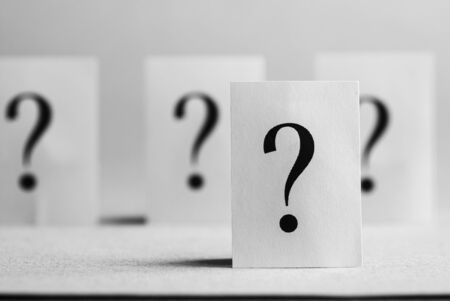 Four question mark cards stood on white background. Stockfoto