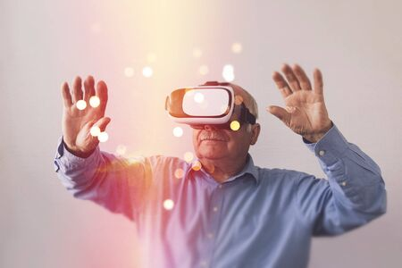 Elderly man wearing a Virtual Reality headset with arms raised and a bokeh of sparkling lights in front of him in a conceptual image