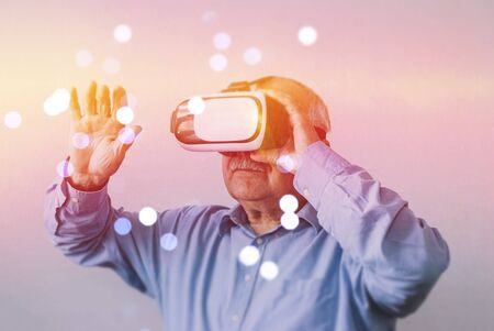 Senior man experiencing a virtual environment wearing a VR headset surrounded by a bokeh of sparkling lights in a colorful aura over a grey background