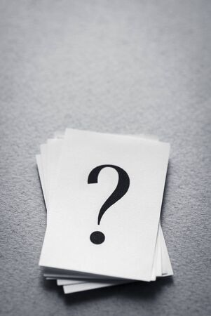 stack of paper cards with a printed question mark on a gray background.
