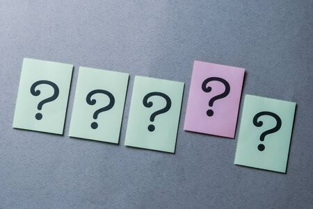 Line of four printed question marks on green paper and one on pink raised above the others in a concept of leadership, diversity and individualism over a grey background