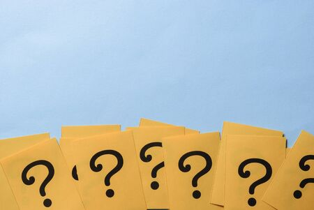 Row of yellow question marks printed on paper or cards forming a lower border over a blue background with copy space