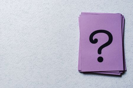 Stack of printed question marks on purple paper arranged to the side on a grey background with copy space