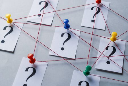 Network of printed question marks on white cards pinned with thumb tacks and joined by string in a conceptual image