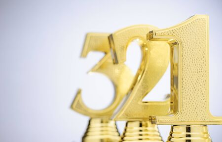 First, Second and Third placed winners trophies in the form of gold numbers in a receding line over white with copy space