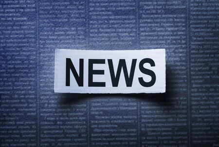 Closeup of news word on white sheet on black background of newspaper