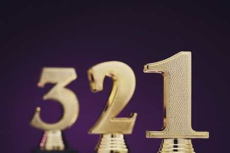 Close up view of three separate slightly blurry golden number trophies in front of dark purple gradient background
