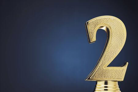 Second place winners gold trophy with a 3D textured metallic number two over blue with copy space