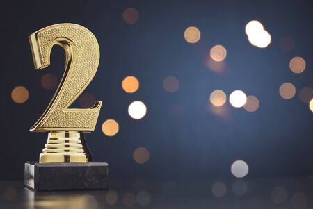 Second place winners gold trophy with a 3D textured metallic number two over blue with copy space and bokeh