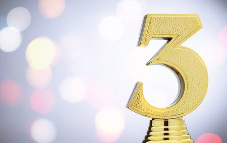 3rd placed runner up metallic gold trophy with a 3D number 3 on white with copy space and bokeh