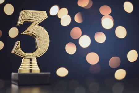 Sharp close up on single isolated gold colored plastic statue of number 3 over blue and black background and bokeh