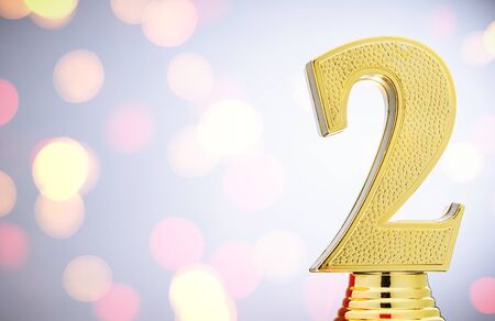 2nd place Runners Up gold trophy in the form of a metallic number one with copy space over a white studio background and bokeh