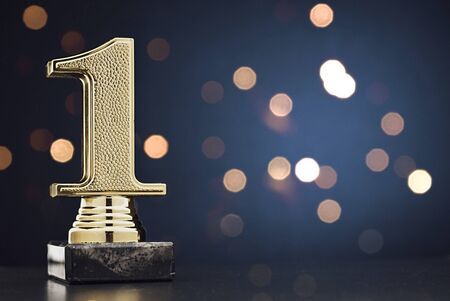 Champion or Winner gold trophy in the shape of a textured 3D number one for 1st place over blue with copy space and bokeh