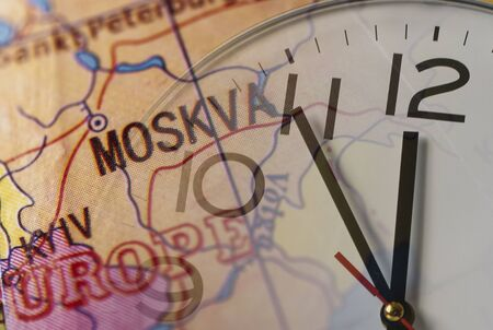 Double exposure of clock and map with European cities Moscow and Kiev