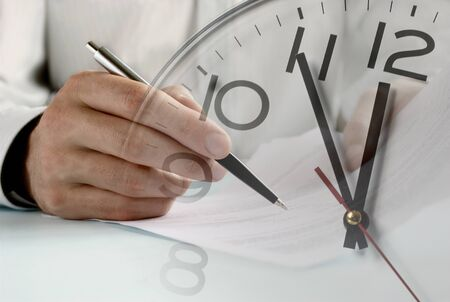 Double exposure of crop male hand with pen doing entries in official papers and clock Reklamní fotografie