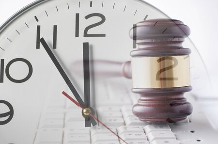 Double exposure of wooden and brass gavel on computer keyboard and clock on white background