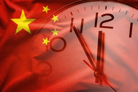 Double exposure of red Chinese flag and clock-face