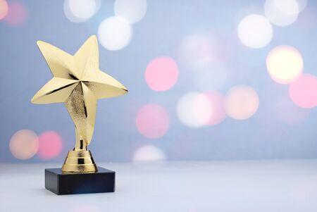 Gewinner oder 1. Platz Gold Trophy Award für eine Meisterschaft oder Sportveranstaltung mit einem Stern auf einem Sockel auf einem weißen Tisch vor einem Bokeh aus funkelnden Lichtern mit Kopierraum