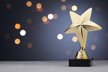 Gold star trophy for a winner or champion of a competition or sporting event placed to the side against a bokeh of sparkling lights with copy space Reklamní fotografie