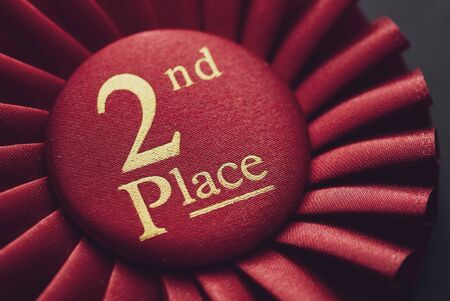 Closeup winner 2nd place red rosette with gold text on black background Reklamní fotografie