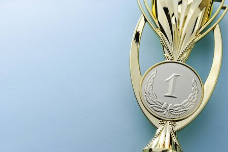Gold medallion winners trophy for the first place winner of a competition of championship event over grey with copy space placed on the right side of the frame