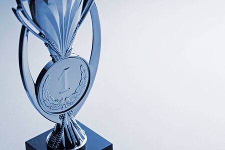 Championship award trophy for the first place winner with a central medallion engraved with a laurel wreath over grey with copy space viewed close up high angle Reklamní fotografie