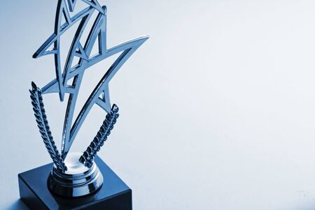 Silver shooting star winners trophy with laurel wreath for a competition or championship over grey with copy space placed as a left border