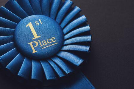 Champion 1. Platz blaue Rosette mit goldenem Text auf schwarzem Hintergrund Standard-Bild