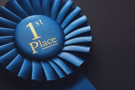 Champion 1st place blue rosette with gold text on black background Stock Photo