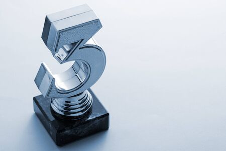Third place runner up silver trophy in the shape of a number three on a plinth placed to the side on grey with copy space or a competition win
