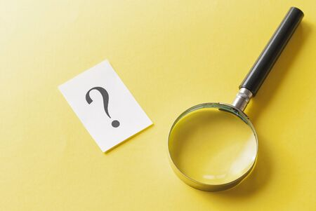 Magnifying glass with printed question mark lying side by side on a yellow background in a conceptual image viewed from above Stock Photo